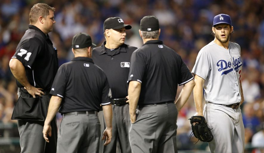 Los Angeles Dodgers starting pitcher Clayton Kershaw, right, listens to the umpire crew as they confer after several lights went out at Wrigley Field during the sixth inning of a baseball game Monday, June 22, 2015, in Chicago. (AP Photo/Charles Rex Arbogast)