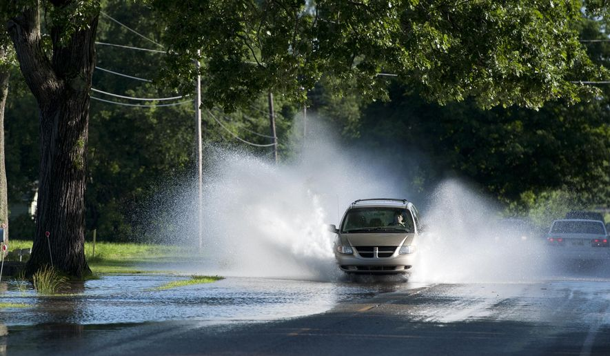 A vehicle moves through water in the road north of Jackson, Mich.,  on Tuesday, June 23, 2015.  A series of severe thunderstorms that pushed damaging winds and tornados into several parts of Michigan wrecked homes and knocked out power to thousands of people, officials said Tuesday. (J. Scott Park/The Jackson Citizen Patriot via AP) ALL LOCAL TELEVISION OUT; LOCAL TELEVISION INTERNET OUT
