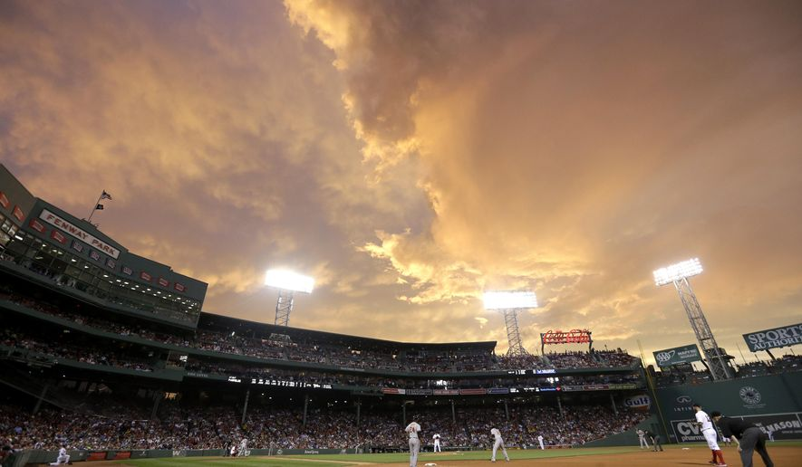 The Baltimore Orioles play the Boston Red Sox in the forth inning of a baseball game under a dramatic sky at Fenway Park, Tuesday, June 23, 2015, in Boston. Severe thunderstorm warnings were issued at mid-evening Tuesday for a new line of storms moving across western and north central Massachusetts and northern Connecticut. (AP Photo/Steven Senne)