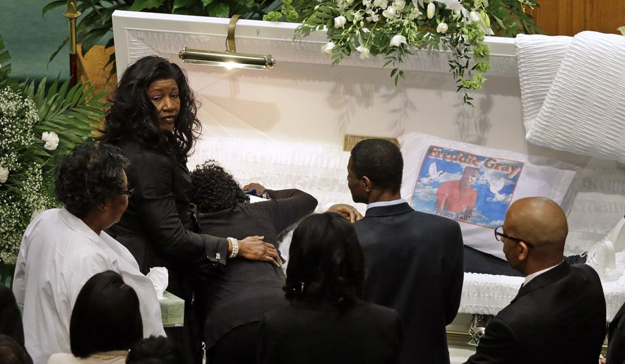 "FILE- In this April 27, 2015, file photo, Gloria Darden, mother of Freddie Gray, is comforted as she embraces his body before his funeral at New Shiloh Baptist Church in Baltimore. A medical examiner found Freddie Gray suffered a ""high-energy injury,"" most likely caused when the Baltimore police van he was riding in braked sharply, according to an autopsy report obtained by The Baltimore Sun. (AP Photo/Patrick Semansky, File)"