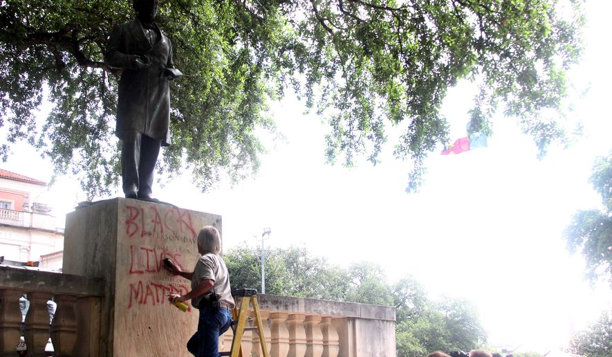 A maintenance worker cleans the Jefferson Davis statue in the Main Mall at the University of Texas at Austin, Tuesday, June 23, 2015. The statue has been defaced at the University of Texas as another push is underway to remove it from the Austin campus. (Tess Cagle/The Daily Texan via AP) ** FILE **