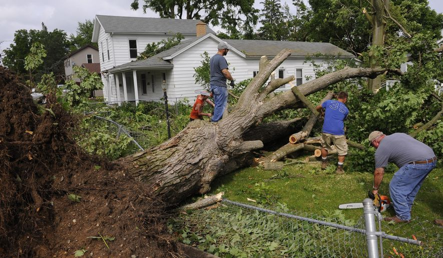 People work together to remove huge fallen trees in Portland, Mich., after severe storms Monday, June 22, 2015. The National Weather Service confirmed late on Monday that Portland had been hit with a tornado rated EF1 with winds of around 100 mph. The storm was part of a string of bad weather that hurtled into Michigan's Lower Peninsula after rushing across the country's Midwest. (Rod Sanford/Lansing State Journal via AP)