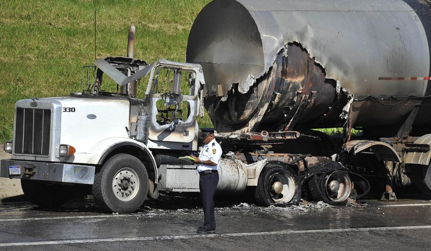 A public safety officer writes notes after a tanker fire on southbound Interstate 75, Tuesday, June 23, 2015, in Detroit. Police say the driver was able to maneuver the vehicle to the shoulder of the freeway's north side near Interstate 94. (Daniel Mears/Detroit News via AP)