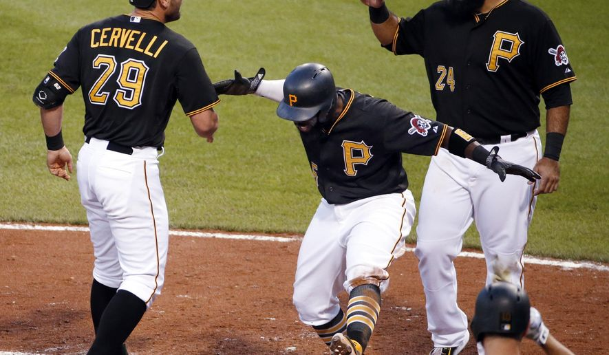 Pittsburgh Pirates' Francisco Cervelli (29) is greeted by teammates Josh Harrison, center, and Pedro Alvarez (24) who were on base for his three-run home run off Cincinnati Reds relief pitcher Pedro Villarreal during the fourth inning of a baseball game in Pittsburgh, Tuesday, June 23, 2015. (AP Photo/Gene J. Puskar)