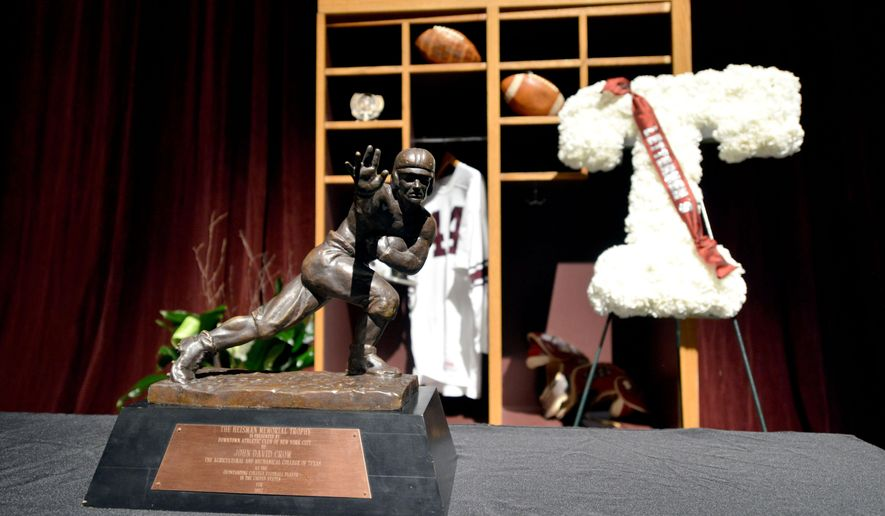 Texas A&M's John David Crow's Heisman trophy sits along side other memorabilia during a memorial service for Crow on Tuesday, June 23, 2015, at Reed Arena in College Station, Texas. Crow, the bruising running back who won the 1957 Heisman Trophy with Texas A&M before a Pro Bowl career in the NFL died at age 79. (Sam Craft/College Station Eagle via AP)