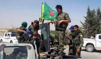 In this photo provided by the Kurdish fighters of the People's Protection Units (YPG), which has been authenticated based on its contents and other AP reporting, Kurdish fighters of the YPG, sit on their pickup in the town of Ein Eissa, north of Raqqa city, Syria, Tuesday, June 23, 2015. Kurdish fighters and their allies have captured an Islamic State group military base in northern Syria under the cover of U.S.-led airstrikes bringing them closer than ever to the extremists de facto capital of Raqqa, activists said Tuesday. (The Kurdish fighters of the People's Protection Units via AP)