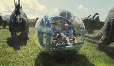 """This photo provided by Universal Pictures shows, Nick Robinson, left, as Zach, and Ty Simpkins as Gray, in a scene from the film, """"Jurassic World,"""" directed by Colin Trevorrow, in the next installment of Steven Spielberg's groundbreaking """"Jurassic Park"""" series. (ILM/Universal Pictures/Amblin Entertainment via AP)"""
