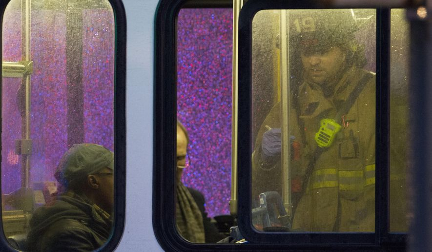 FILE - In this Jan. 12, 2015, file photo, a firefighter attends people on a bus to assess triage needs after people were evacuated from a smoke filled Metro subway tunnel in Washington. Federal transportation safety officials will be gathering information about a fatal malfunction on Washington's subway system during a rare investigative hearing. One woman died and more than 80 others were sickened by smoke after an electrical malfunction in January caused a train to fill with smoke while it stopped in a tunnel in downtown Washington.  (AP Photo/Jacquelyn Martin, File)