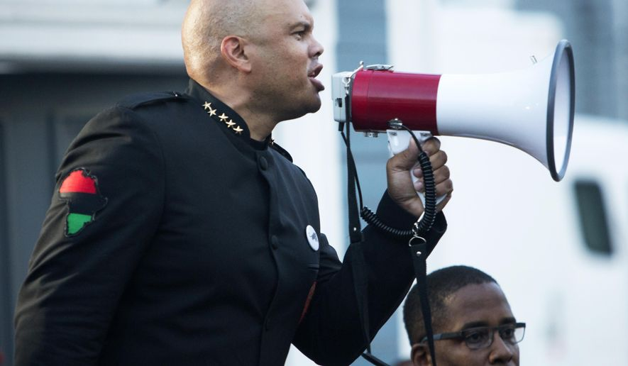Hashim Nzinga, left, a marcher who identified himself as national chairman of the New Black Panther party, gives a speech in front of Emanuel AME Church in Charleston, S.C., Tuesday, June 23, 2015. The march comes six days after a gunman shot nine people during bible study inside the church. (AP Photo/Mic Smith)