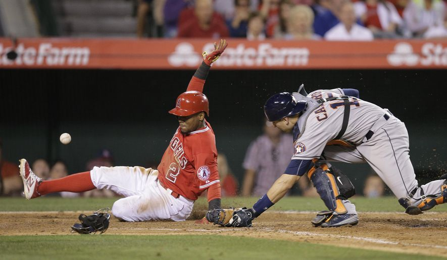 Los Angeles Angels' Erick Aybar, left, scores on a sacrifice bunt by Daniel Robertson as Houston Astros catcher Jason Castro misses the throw during the eighth inning of a baseball game, Monday, June 22, 2015, in Anaheim, Calif. (AP Photo/Jae C. Hong)