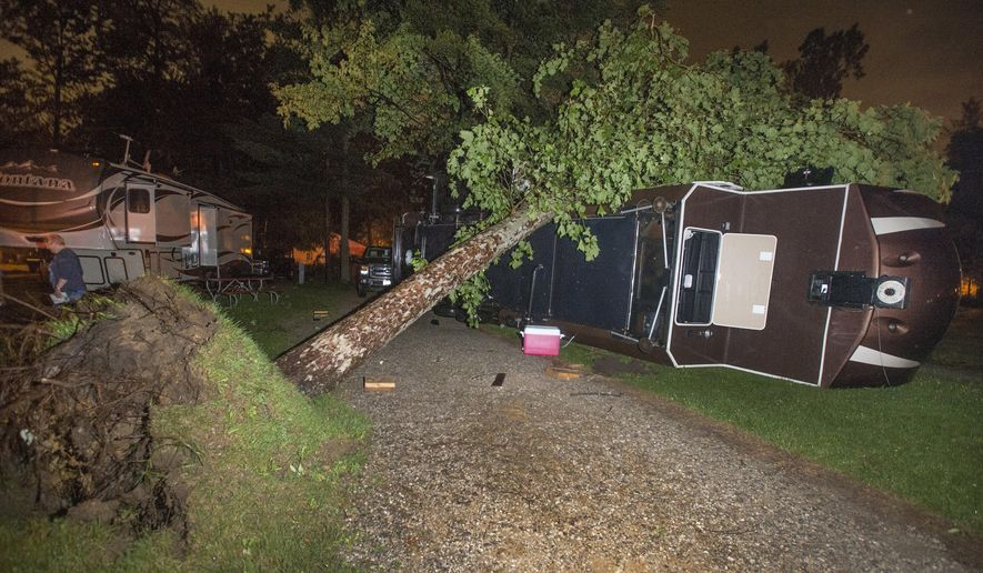 A tree lies on top of a camper that was overturned at Pine Ridge RV Campground in Birch Run Township after a tornado swept through Saginaw and Tuscola Counties Monday night, June 22, 2015. The occupants of the RV suffered minor injuries and were taken to a hospital. (Jeff Schrier/The Saginaw News/MLive.com via AP)