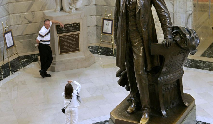 FILE - In this Aug. 5, 2008, file photo, tourists pose for pictures in front of the Jefferson Davis statue in the Capitol Rotunda as a statue of Abraham Lincoln towers in the foreground in Frankfort, Ky. The Republican nominee for governor, Matt Bevin, said Tuesday, June 23, 2015, the state should remove the Davis statue but Democratic nominee Jack Conway, Kentucky's attorney general, said he would have to think about whether to remove it. (AP Photo/Ed Reinke, File)