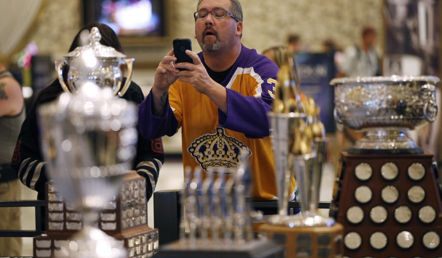 A fan takes pictures of NHL award trophies on display at the MGM Grand on Tuesday, June 23, 2015, in Las Vegas. The growing possibility of NHL expansion to Las Vegas is a popular topic among players and executives this week with the league in town for its postseason awards show and executive meetings. The league could even announce the opening of a formal expansion process Wednesday. (AP Photo/John Locher)