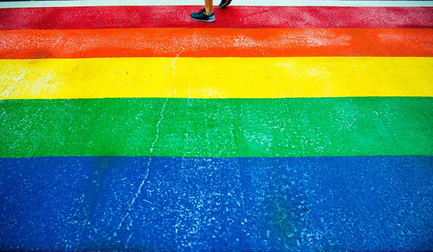 "A pedestrian walks on the newly-installed, rainbow-colored crosswalk for Pride Week in Seattle on Tuesday, June 23, 2015.   Mayor Ed Murray unveiled one of the 11 new crosswalks in the historically gay-friendly Capitol Hill neighborhood on Tuesday. He says the display ""says something about Seattle"": that's a city of diverse neighborhoods and character.  (AP Photo/seattlepi.com, Jordan Stead)"