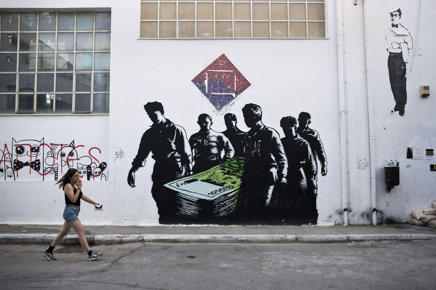 """In this photo taken on Wednesday, June 17, 2015, a woman walks past a graffiti artwork titled """"Death of Euros"""" made by French street artist Goin at the Athens School of Fine Arts. Over the past five years of Greece's economic depression, more and more paintings comment on the country's financial and social woes. (AP Photo/Petros Giannakouris)"""