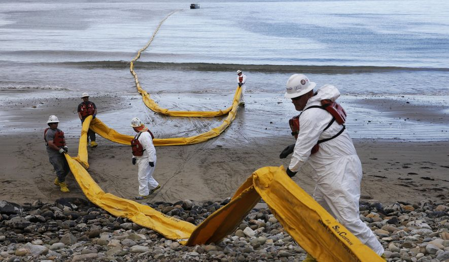 In this May 21, 2015, file photo, workers prepare an oil containment boom at Refugio State Beach, north of Goleta, Calif. The shutdown of a pipeline that spilled up to 101,000 gallons of crude on the Santa Barbara coast forced Exxon Mobil Corp. to halt operations at three offshore platforms because it couldn't deliver oil to refineries, the company said Tuesday, June 23, 2016, file photo. (AP Photo/Jae C. Hong, File)