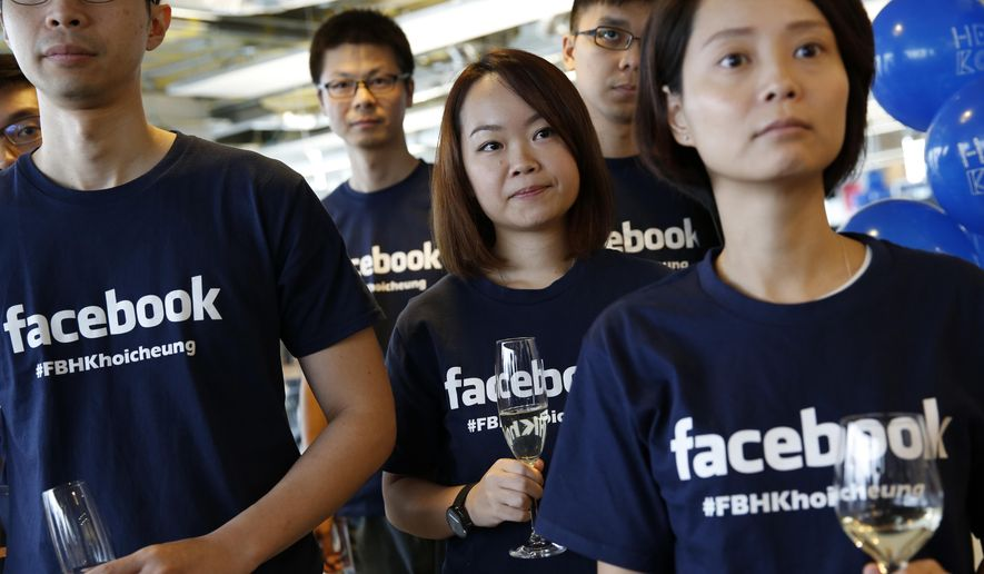 FILE - In this July 24, 2014 file photo, Facebook staff members attend the opening ceremony of their new office in Hong Kong. The world's biggest online social network knocked Wal-Mart, the world's largest retailer, out of the top 10 list of the highest-valued companies in the Standard & Poor's 500 index on Monday, June 22, 2015, and the gap widened on Tuesday. (AP Photo/Kin Cheung, File)