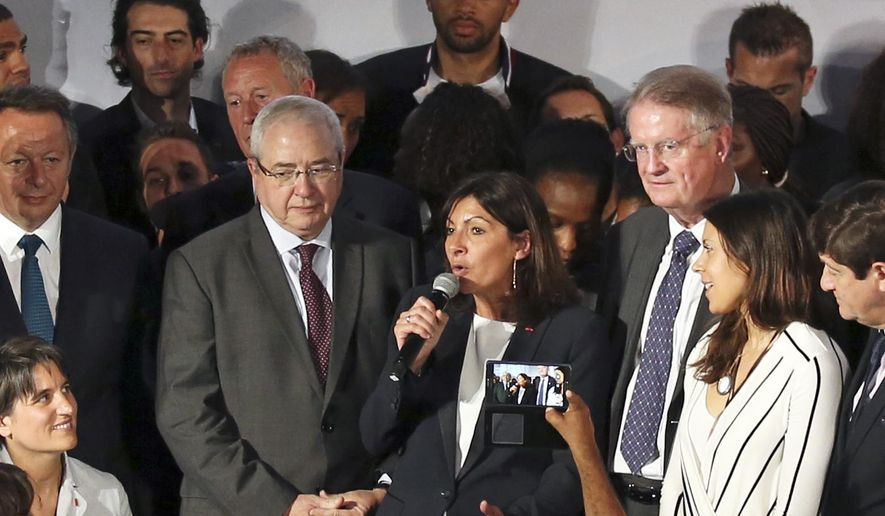 Paris mayor Anne Hidalgo, center, announces the candidacy of Paris for the 2024 Olympic games, in Paris, Tuesday June 23, 2015. Paris declared its candidacy for the 2024 Olympics on Tuesday, becoming the fourth city to enter the race and setting out its vision for bringing the games back to the French capital for the first time in 100 years. Standing at left is the President of Paris region Jean-Paul Huchon and at right the President of the International Rugby Federation Bernard Lapasset. (AP Photo/Remy de la Mauviniere)