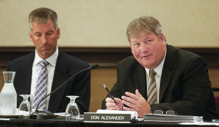 The Kansas State Lottery Gaming Facility Review Board's Don Alexander, right, alongside  Jeff Oakes, asks questions of a consultant on Tuesday June 23, 2015, at the Downtown Ramada Hotel and Convention Center in Topeka, Kan., before hearing three proposals for the construction of a casino in Southeast Kan. (Chris Neal/Topeka Capital-Journal via AP)
