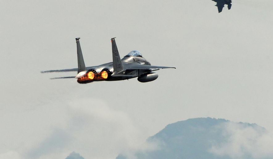 A pair of F-15C Eagles from the 18th Wing at Kadena Air Base, in Japan, take off from Joint Base Elmendorf-Richardson near Anchorage, Alaska, Tuesday, June 23, 2015, while participating in Northern Edge, a joint training exercise. (Bill Roth/Alaska Dispatch News via AP)