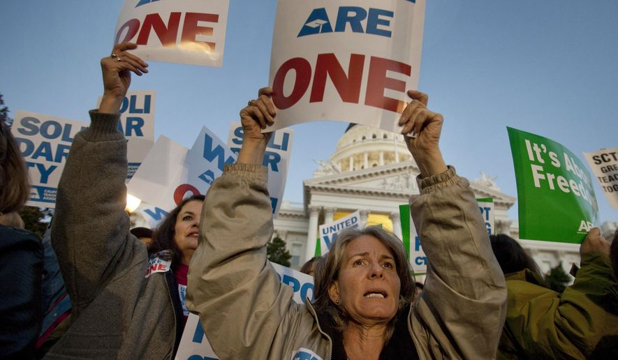 FILE - In this Feb. 22, 2011, file photo, Karen Wallace, right, and Meryleigh Brainerd, left, both teachers in Calaveras County, join in a candlelight vigil in front of the state Capitol to express sympathy with union members in Wisconsin in Sacramento, Calif. Powerful public-sector unions are facing another high-profile legal challenge that they say could wipe away millions from their bank accounts and make it tougher for them to survive. A group of California schoolteachers, backed by a conservative group, has asked the Supreme Court to rule that unions representing government workers can't collect fees from those who choose not to join. The case comes as officials in Wisconsin and other states dealing with budged deficits have worked to reduce bargaining rights for public employees. (AP Photo/Robert Durell, File)