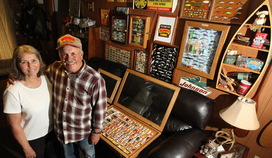 In this May 14, 2015, photo,  Diana Boyer and her husband Dave Boyer of Strasburg display their individual fishing lure collections at their home in Strasburg, Ill. Their two collections combined exceed 550 lures.(Jim Bowling/Herald & Review via AP)