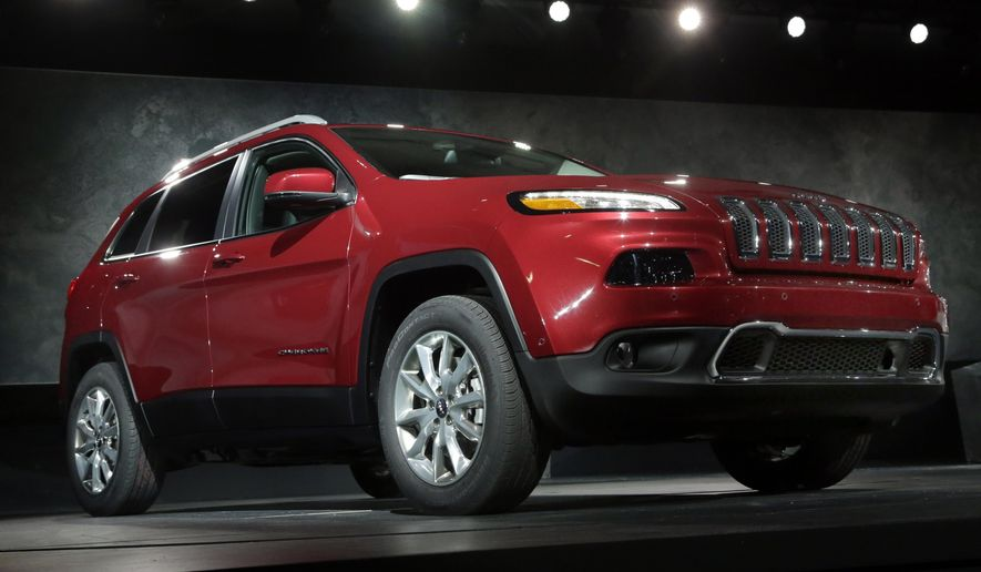 In this March 27, 2013 file photo, the 2014 Jeep Cherokee Limited is presented at the New York International Auto Show, in New York's Javits Center. Fiat Chrysler on Wednesday, June 24, 2015, said it is recalling 164,000 2014 and 2015 model year Jeep Cherokee SUVs worldwide to install shields that stop water from getting into the power rear lift gate controls. (AP Photo/Richard Drew, File)