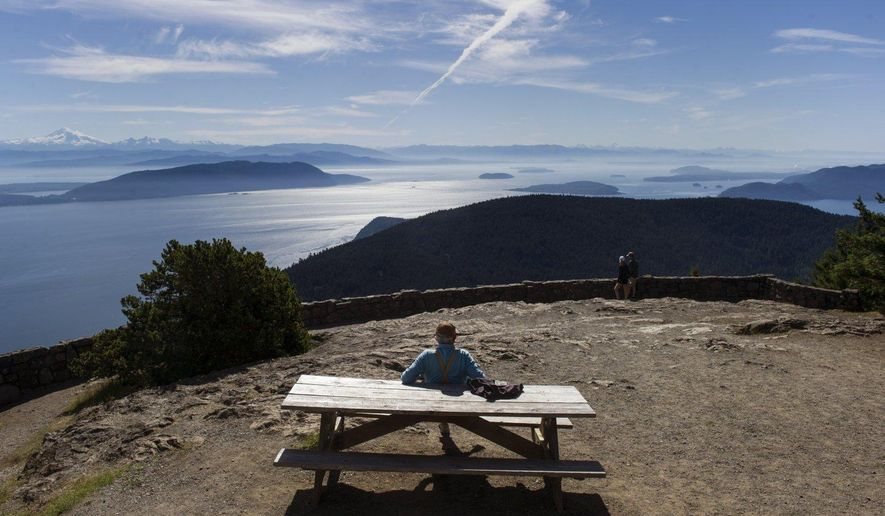 In this July 1, 2014 photo, a visitor sits on top of Mount Constitution in Washington, part of Moran State Park and the highest point of the San Juan Islands. (Maddie Meyer/The Seattle Times via AP) SEATTLE OUT; USA TODAY OUT; MAGS OUT; TELEVISION OUT; NO SALES; MANDATORY CREDIT TO BOTH THE SEATTLE TIMES AND THE PHOTOGRAPHER