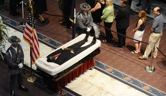 South Carolina Highway Patrol honor guards stand over Sen. Clementa Pinckney's body as members of the public file past in the Statehouse, Wednesday, June 24, 2015, in Columbia, S.C.  President Barack Obama is scheduled to deliver the eulogy at Pinckney's funeral Friday morning at the College of Charleston. (AP Photo/Rainier Ehrhardt)