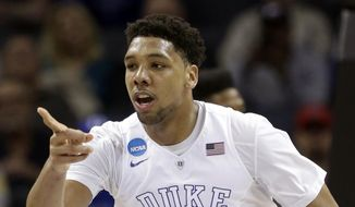 FILE - In this March 22, 2015, file photo, Duke's Jahlil Okafor (15) points to a teammate after a basket against San Diego State during the second half of an NCAA tournament college basketball game in the Round of 32 in Charlotte, N.C. Okafor is a top prospect in the NBA draft on Thursday, June 25, 2015. (AP Photo/Gerald Herbert, File)