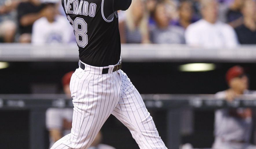 Colorado Rockies' Nolan Arenado follows the flight of his solo home run off Arizona Diamondbacks starting pitcher Chase Anderson to lead off the bottom of the fourth inning of a baseball game Tuesday, June 23, 2015, in Denver. (AP Photo/David Zalubowski)