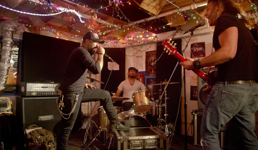 "In a Thursday, June 4, 2015 photo, members of the Iraqi heavy metal band ""Acrassicauda,"" lead vocalist Faisal Mustafa, left, drummer Marwan Hussein, center, and guitarist Muhammad Al Ansari, rehearse in New York. The band formed in July 2000 in Baghdad, Iraq.  ""We have been refugees since 2006,"" said Hussein, an exodus which produced the album ""Only the Dead See the End of the War.""  (AP Photo/Bebeto Matthews)"
