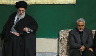 In this photo released by an official website of the office of the Iranian supreme leader, commander of Iran's Quds Force, Qassem Soleimani, right, sits next to the Supreme Leader Ayatollah Ali Khamenei while attending a religious ceremony in a mosque at his residence in Tehran, Iran, Friday, March 27, 2015. (AP Photo/Office of the Iranian Supreme Leader)