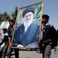 In a show of support, Iraqi Hezbollah scouts parade with a portrait of Iran's supreme leader, Ayatollah Ali Khamenei. Iran's most violent proxy militia in Iraq has vowed to start killing Americans again once the Islamic State is expelled. (Associated Press/File)