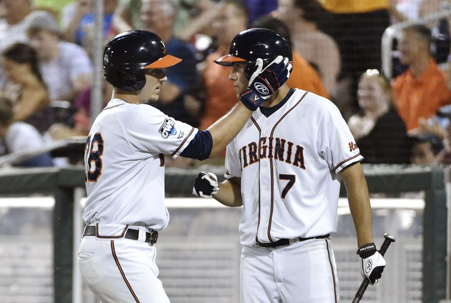 Virginia pitcher Kevin Doherty, left, celebrates with Adam Haseley (7) after scoring on a Thomas Woodruff two-run single against Vanderbilt during the sixth inning of Game 2 of the best-of-three NCAA baseball College World Series finals at TD Ameritrade Park in Omaha, Neb., Tuesday, June 23, 2015. (AP Photo/Mike Theiler)