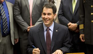 Wisconsin Gov. Scott Walker signs a gun bill at the Milwaukee County Sheriff's office that eliminates a 48-hour waiting period for handgun purchases. Wednesday, June. 24, 2015, in Milwaukee. (AP Photo/Jeffrey Phelps) ** FILE **