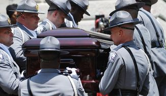A South Carolina Highway Patrol honor guard carries Sen. Clementa Pinckney's casket to the Statehouse, Wednesday, June 24, 2015, in Columbia, S.C. Pinckney's open coffin was being put on display under the dome where he served the state for nearly 20 years. Pinckney was one of those killed in a mass shooting at the Emanuel AME Church in Charleston. (AP Photo/Rainier Ehrhardt)