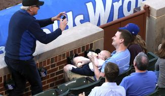 In this photo taken Tuesday, June 23, 2015, baseball fan Keith Hartley, center, is photographed by another fan, after he caught a foul ball while bottle-feeding his 7-month-old son during the second inning of baseball game between the Chicago Cubs and the Los Angeles Dodgers at Wrigley field in Chicago. (Nuccio DiNuzzo/Chicago Tribune via AP) MANDATORY CREDIT CHICAGO TRIBUNE; CHICAGO SUN-TIMES OUT; DAILY HERALD OUT; NORTHWEST HERALD OUT; THE HERALD-NEWS OUT; DAILY CHRONICLE OUT; THE TIMES OF NORTHWEST INDIANA OUT; TV OUT; MAGS OUT; NO SALES