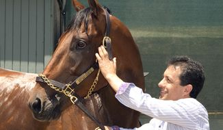 In a photo provided by Benoit Photo, jockey Victor Espinoza poses for photos with Triple Crown-winner American Pharoah on Thursday, June 18, 2015, at Santa Anita in Arcadia, Calif., after a flight from Kentucky and a police escort from the airport. (Benoit Photo via AP)