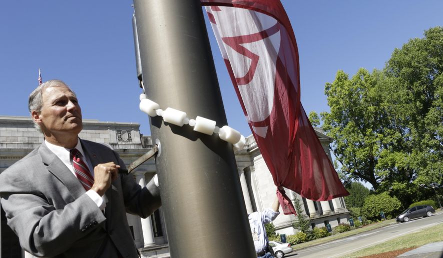 Gov. Jay Inslee raises the flag of Washington State University in honor of its late president, Elson Floyd, Thursday, June 25, 2015, in Olympia, Wash. Floyd died last weekend from complications of colon cancer. (AP Photo/Rachel La Corte)