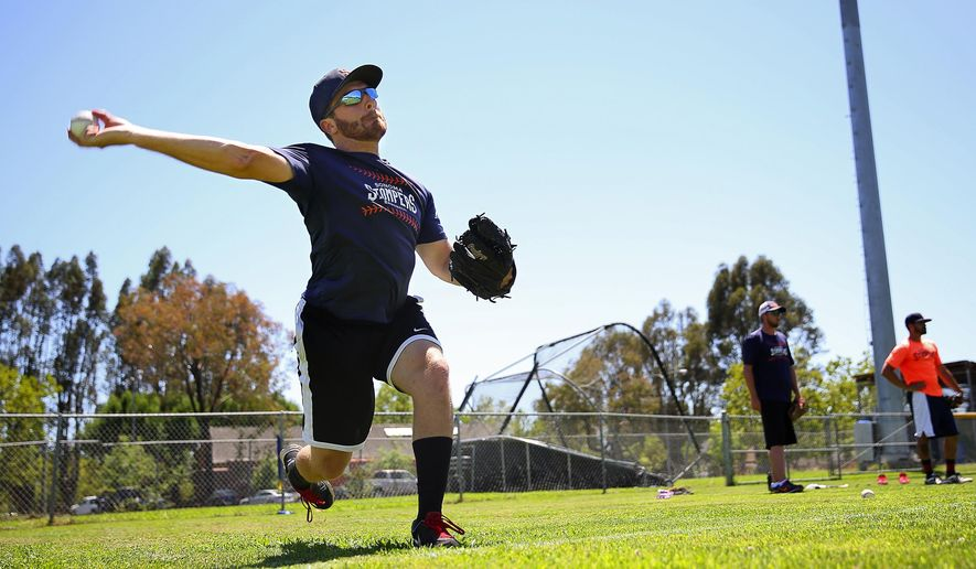 Sonoma Stompers pitcher Sean Conroy, left, warms up during practice at Arnold Field, in Sonoma, Calif. on Tuesday, June 23, 2015.  Conroy, 23, of Clifton Park, N.Y., is the first openly gay player to enter the professional baseball ranks, according to the Stompers.   (Christopher Chung/ The Press Democrat via AP)