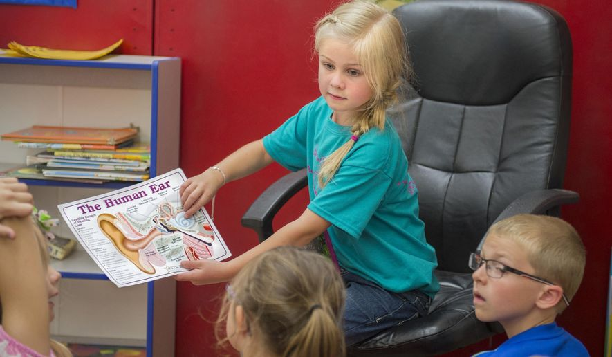 ADVANCE FOR USE SATURDAY, JUNE 27 AND THEREAFTER - In this May 18, 2015 photo, Sawyer Drury uses a graphic to explain her deafness to her first grade classmates in Brimfield, Ill. Drury, 7, was born with profound hearing loss but, with the help of hearing aids and work with Sarah Moon, her speech pathologist, has excelled despite the impairment.  (David Zalaznick/Journal Star via AP)