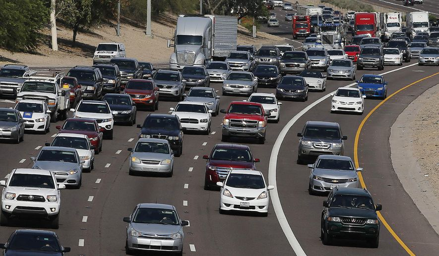 Afternoon rush hour traffic heads out of  town Wednesday, June 24, 2015, in Phoenix. An estimated 41.9 million people will travel 50 miles or more from home during the Independence Day holiday weekend, up 0.7 percent from last year and the most since 2007, according to travel agency and car lobbying group AAA. (AP Photo/Ross D. Franklin)