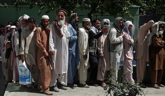 Afghan men wait in line to receive food donation during the holy month of Ramadan in Kabul, Afghanistan, Thursday, June 25, 2015. Muslims throughout the world are marking the month of Ramadan, the holiest month in the Islamic calendar during which devotees fast from dawn till dusk. (AP Photo/Massoud Hossaini) ** FILE **