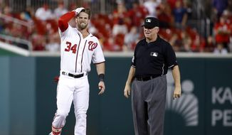 Washington Nationals' Bryce Harper grimaces after running to second base for a double during the 11th inning of a baseball game against the Atlanta Braves at Nationals Park, Wednesday, June 24, 2015, in Washington. Nationals manager Matt Williams and trainer Lee Kuntz checked on him, but he remained in the game. Harper later scored on a sacrifice fly by Ian Desmond. The Nationals won 2-1. (AP Photo/Alex Brandon)