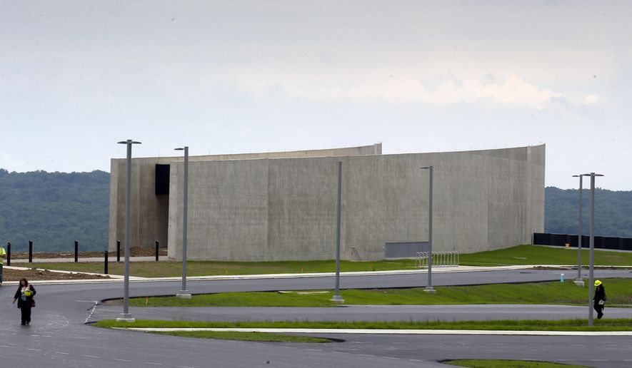 Reporters walk past the visitors center building at the Flight 93 National Memorial, in Shanksville, Pa. during a press tour of the ongoing construction, Thursday, June 25, 2015. The $26 million visitor center complex is scheduled to be dedicated and open to the public Sept. 10, 2015, a day before the 14th anniversary of the terror attacks during which passengers caused the hijacked airliner to crash there. (AP Photo/Keith Srakocic)
