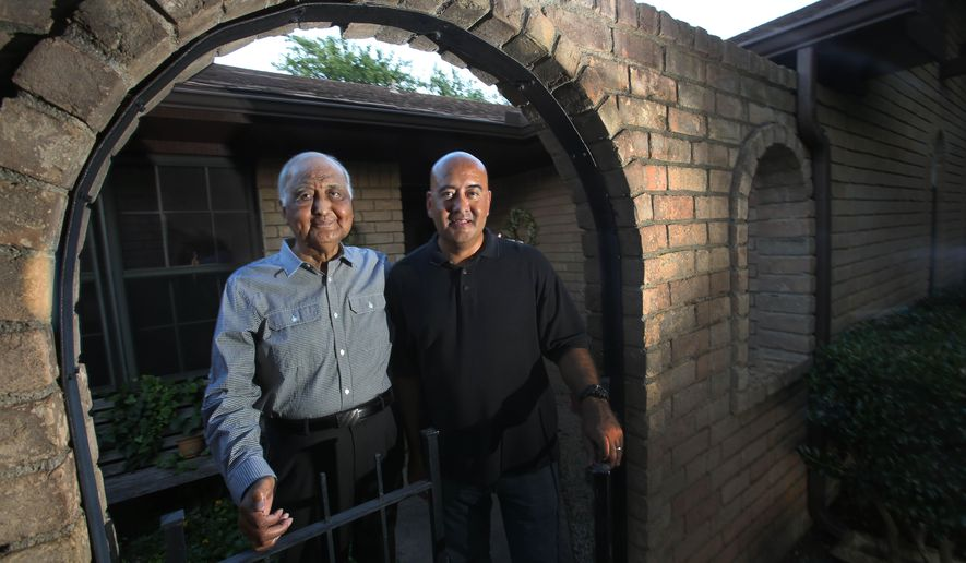 In this June 18, 2015 photo, Moses Cabrera, left, who had polycystic kidney disease (PKD), poses for photo with his son Moses Jr. outside his home in Arlington, Texas. PKD is a hereditary condition that eventually destroys the organ if left untreated. In the late 1980s, Moses Cabrera underwent a kidney transplant and it's been smooth going since -- an experience that has helped him guide son, a Grapevine police office who was also diagnosed with PKD. (Louis DeLuca/The Dallas Morning News via AP) MANDATORY CREDIT; MAGS OUT; TV OUT; INTERNET USE BY AP MEMBERS ONLY; NO SALES