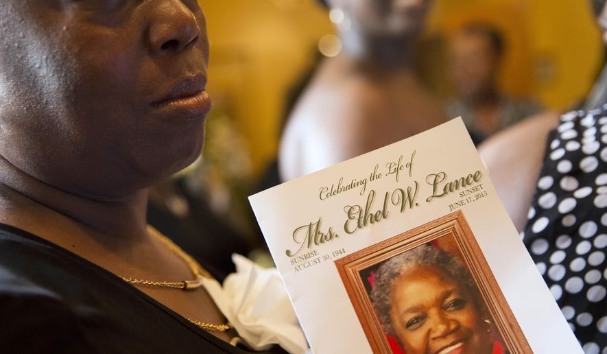 A mourner carries a program while walking in for for the funeral service for Ethel Lance, 70, one of the nine people killed in the shooting at Emanuel AME Church last week in Charleston, Thursday, June 25, 2015, in North Charleston, S.C. (AP Photo/David Goldman) (AP Photo/David Goldman)