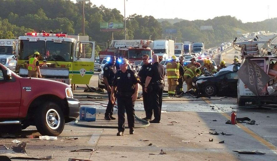 This photo provided by the Chattanooga Police Department shows police and emergency workers at the scene of a nine-vehicle wreck on Interstate 75 near Ooltewah, Tenn, a suburb of Chattanooga. Police in southeastern Tennessee say six people have been killed in the wreck. (Chattanooga Police Department via AP)