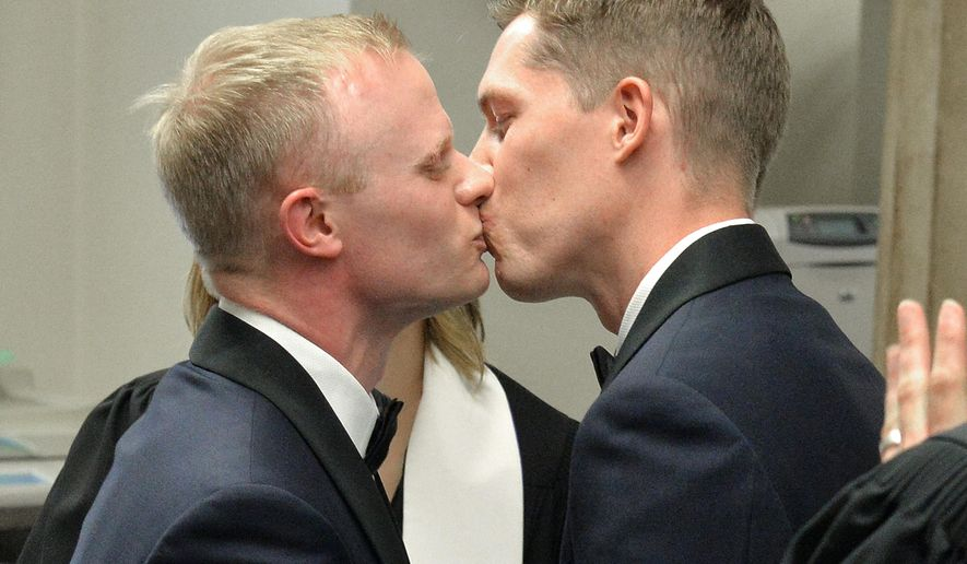 Benjamin Moore, left, and Tadd Roberts kiss after their marriage ceremony at the Jefferson County Clerks Office Friday, June 26, 2015, in Louisville, Ky. The U.S. Supreme Court on Friday ruled that there is a right to same-sex marriage in all 50 states across the country. (AP Photo/Timothy D. Easley)